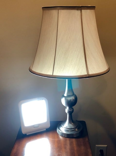 Happy light sitting on end table beside lamp