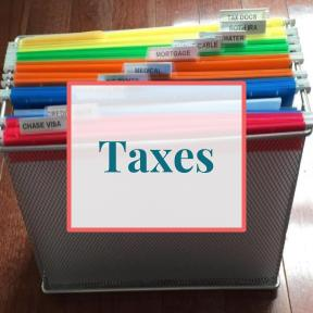 "Labeled and organized file folders in bin with text overlay that reads ""taxes"""